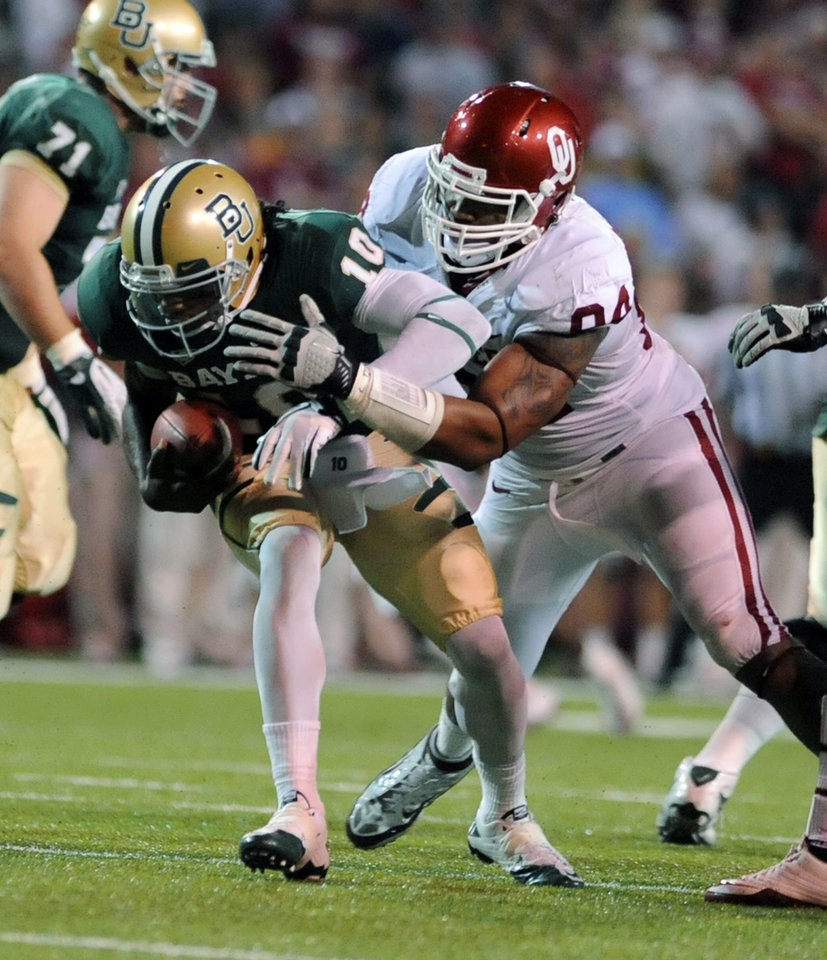 Photo - Oklahoma's Frank Alexander, right, sacks Baylor quarterback Robert Griffin III, left, in the first half of an NCAA college football game, Saturday, Nov. 19, 2011, in Waco, Texas. (AP Photo/Waco Tribune Herald, Rod Aydelotte)