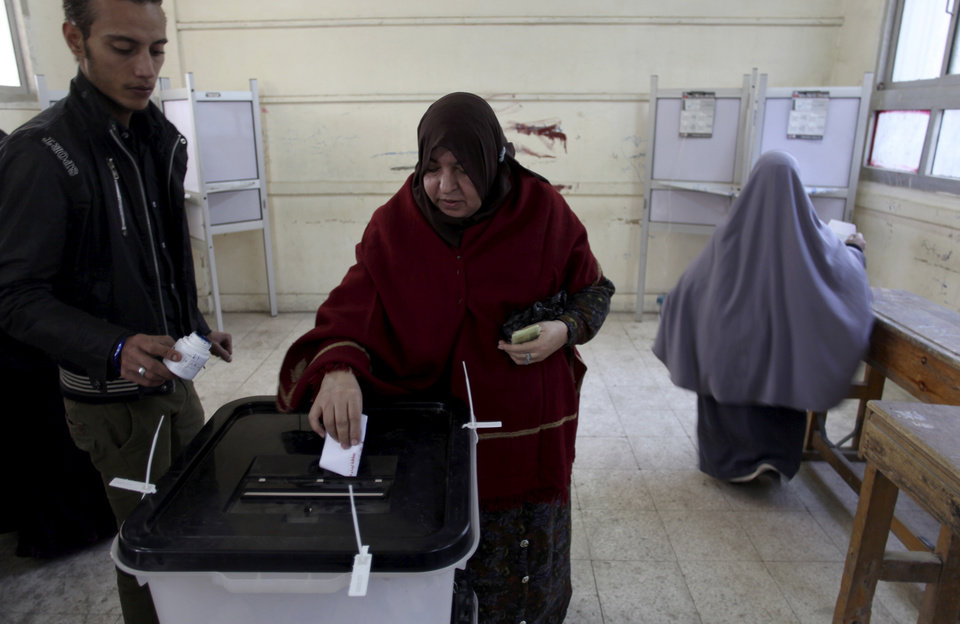 An Egyptian woman casts her vote during a referendum on a disputed constitution drafted by Islamist supporters of President Morsi in Cairo, Egypt, Saturday, Dec. 15, 2012. (AP Photo/Khalil Hamra)