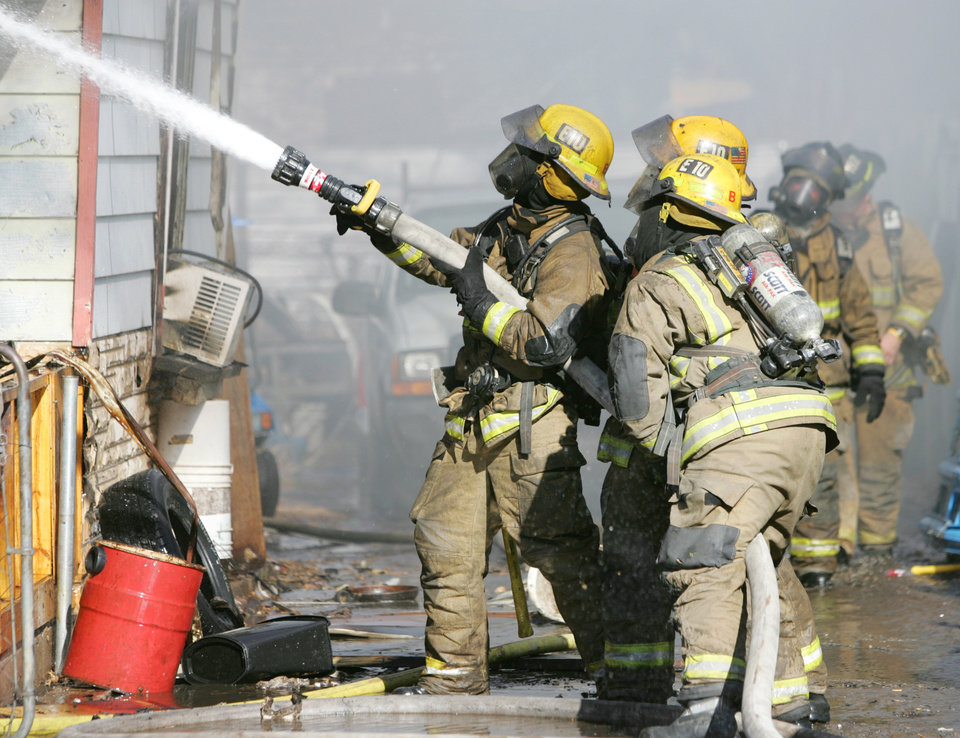 Firefighters battle a house fire Monday morning. PHOTO BY STEVE GOOCH, THE OKLAHOMAN