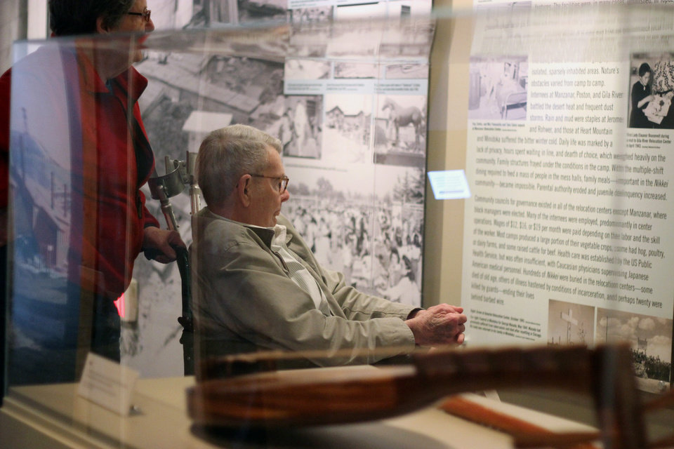 """Photo - In this March 26, 2014 photo, Nancy and Charles Hardy read about the experience of Japanese-Americans sent to internment camps during World War II as they enter an exhibit titled """"Barbed Wire to Battlefields"""" at the National World War II Museum in New Orleans. (AP Photo/Janet McConnaughey)"""