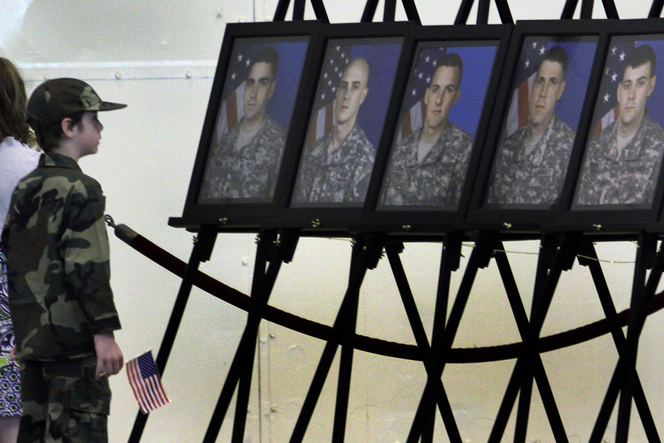 Seven year old Dylan Lewis of Cushing looks at portraits of soldiers who died during their deployment during the return ceremony for the National Guard's 45th Infantry Brigade Combat Team at the Army Aviation hanger at Will Rogers Air National Guard Base Sunday, March 25th, 2012. PHOTO BY HUGH SCOTT, FOR THE OKLAHOMAN
