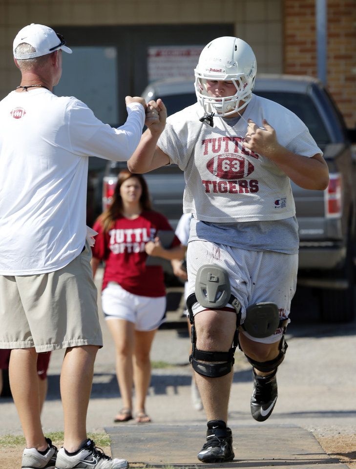 Photo - New head coach Brad Ballard gives a fist bump to Trevor Gillispie during high school football practice on Tuesday, Aug. 12, 2014 in Tuttle, Okla. Photo by Steve Sisney, The Oklahoman