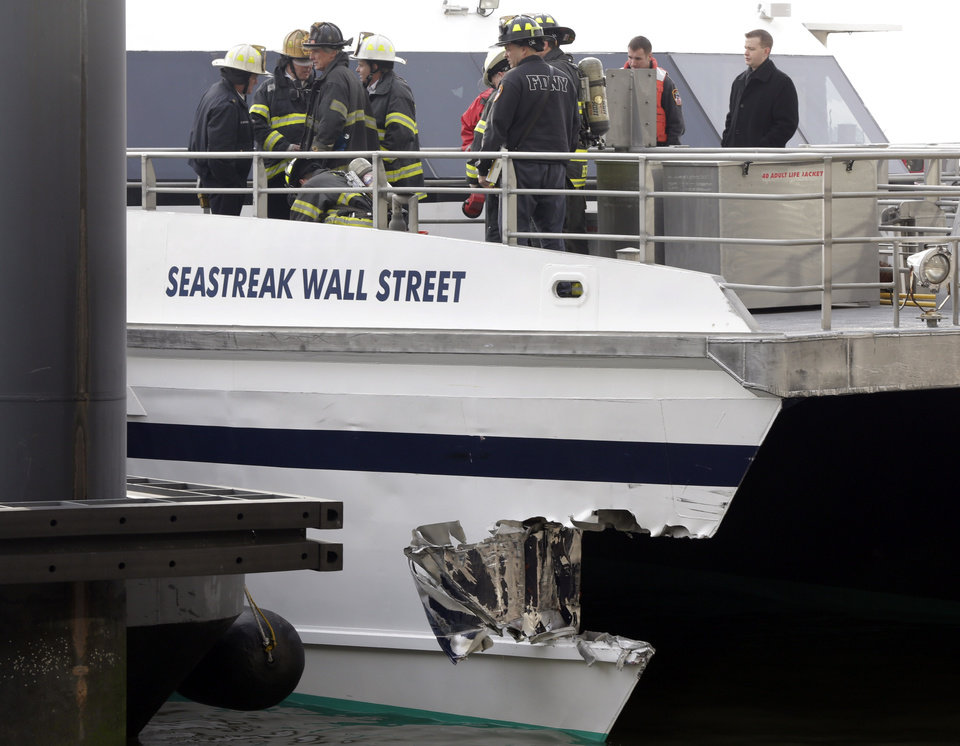 Photo - New York City firefighters walk the deck of the Seastreak Wall Street ferry in New York,  Wednesday, Jan. 9, 2013. The ferry from Atlantic Highlands, N.J., banged into the mooring as it arrived at South Street in lower Manhattan during morning rush hour, injuring as many as 50 people, at least one critically, officials said.(AP Photo/Richard Drew)