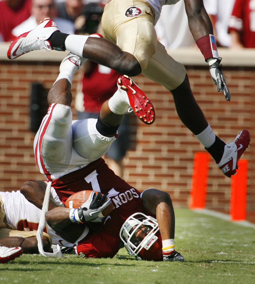 Photo - DeMarco Murray (7) is tackled by Greg Reid (5) as Christian Jones (7) leaps over them during the first half of the college football game between the University of Oklahoma Sooners (OU) and Florida State University Seminoles (FSU) at the Gaylord Family-Oklahoma Memorial Stadium on Saturday, Sept. 11 2010, in Norman, Okla.   Photo by Steve Sisney, The Oklahoman