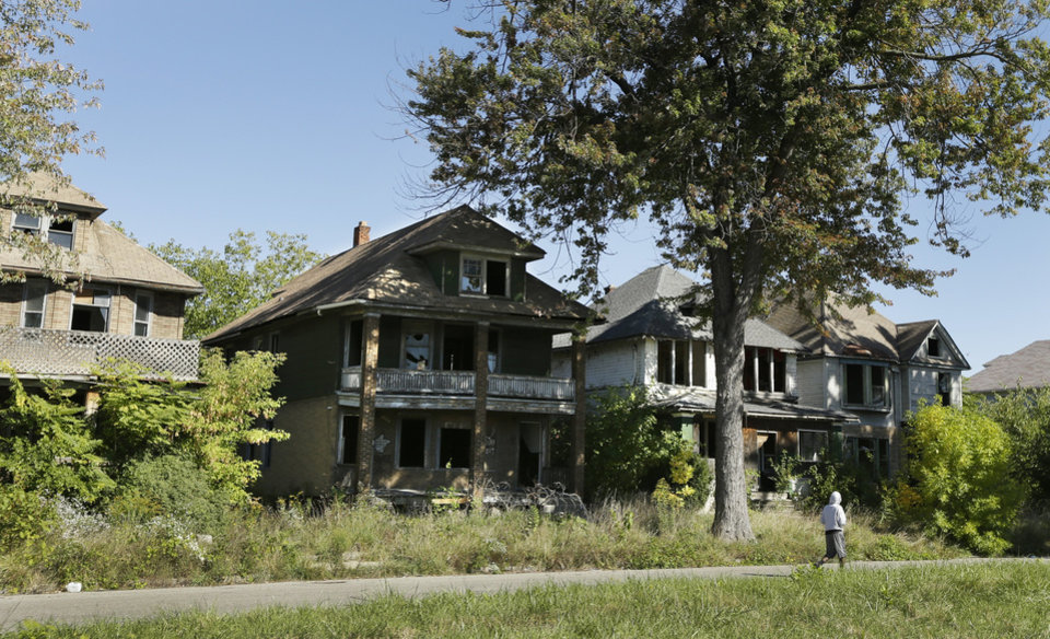 Photo - FILE - In this Sept. 26, 2013 file photo a young man walks in front of a row of abandoned houses in Detroit. Detroit has thousands of decrepit and abandoned homes and buildings. The city's proposal to emerge from bankruptcy includes a plan to demolish them. (AP Photo/Carlos Osorio, File)