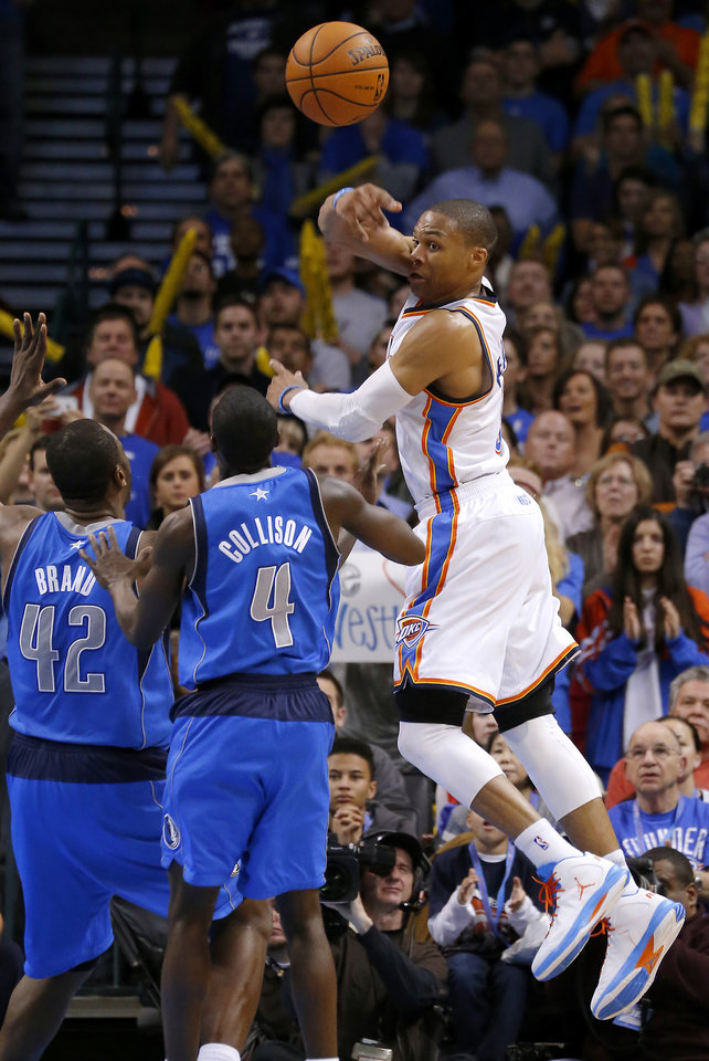 Photo - Oklahoma City's Russell Westbrook (0) passes the ball over Dallas' Elton Brand (42) and Darren Collison (4) during an NBA basketball game between the Oklahoma City Thunder and the Dallas Mavericks at Chesapeake Energy Arena in Oklahoma City, Thursday, Dec. 27, 2012.  Oklahoma City won 111-105. Photo by Bryan Terry, The Oklahoman