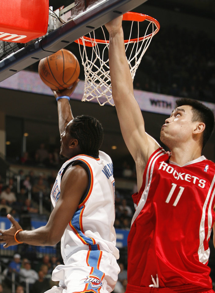 Photo - Kyle Weaver drives under the block of Yao Ming in the first half as the Oklahoma City Thunder plays the Houston Rockets at the Ford Center in Oklahoma City, Okla. on Friday, January 9, 2009. 
