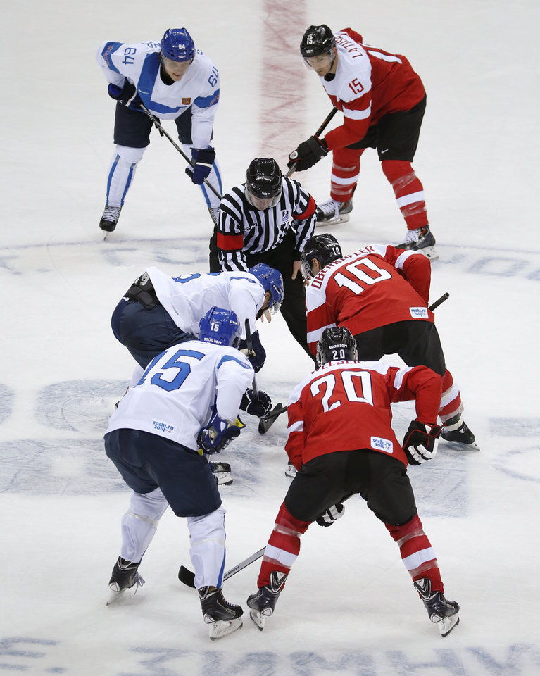 Photo - Team Finland and team Austria face off at the start of a men's ice hockey game at the 2014 Winter Olympics, Thursday, Feb. 13, 2014, in Sochi, Russia. (AP Photo/Mark Humphrey)