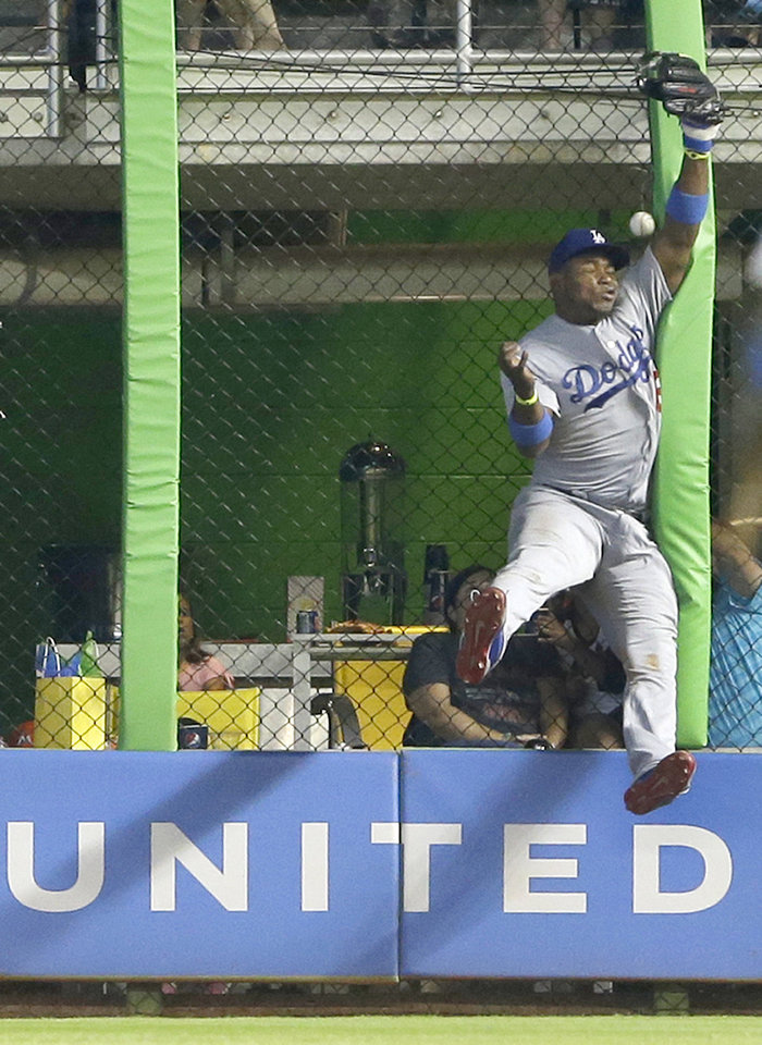 Photo - Los Angeles Dodgers right fielder Yasiel Puig is unable to catch a ball at the fence hit by Miami Marlins' Jeff Baker for a double, during the ninth inning of a baseball game, Sunday, May 4, 2014 in Miami. Puig retreated and made a leaping try for an acrobatic catch but slammed against the fence, and the ball deflected off it and hit him in the face. Puig collapsed to his stomach and was slow to rise, and he walked off the field with an arm around a trainer. Adeiny Hechavarria scored on the play as the Marlins defeated the Dodgers 5-4. (AP Photo/Wilfredo Lee)