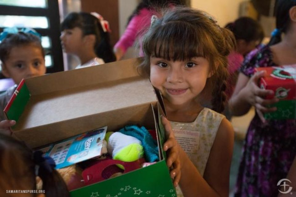 Photo -  A child shows her gift-filled shoebox during an Operation Christmas Child shoebox distribution at Iglesia Apostolica de la Fe en Cristo Jesus in Mazatlan, Mexico. [Samaritan's Purse]