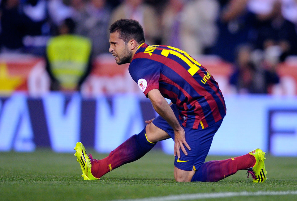 Photo - Barcelona's Jordi Alba grimaces while holding his leg during the final of the Copa del Rey between FC Barcelona and Real Madrid at the Mestalla stadium in Valencia, Spain, Wednesday, April 16, 2014. (AP Photo/Manu Fernandez)