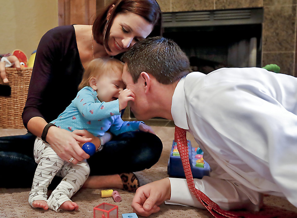 Photo - Kyle and Becky Endicott play with their daughter Julia, 10 months. Julia was concieved using in vitro fertilization.  Photo by Chris Landsberger, The Oklahoman  CHRIS LANDSBERGER -  CHRIS LANDSBERGER