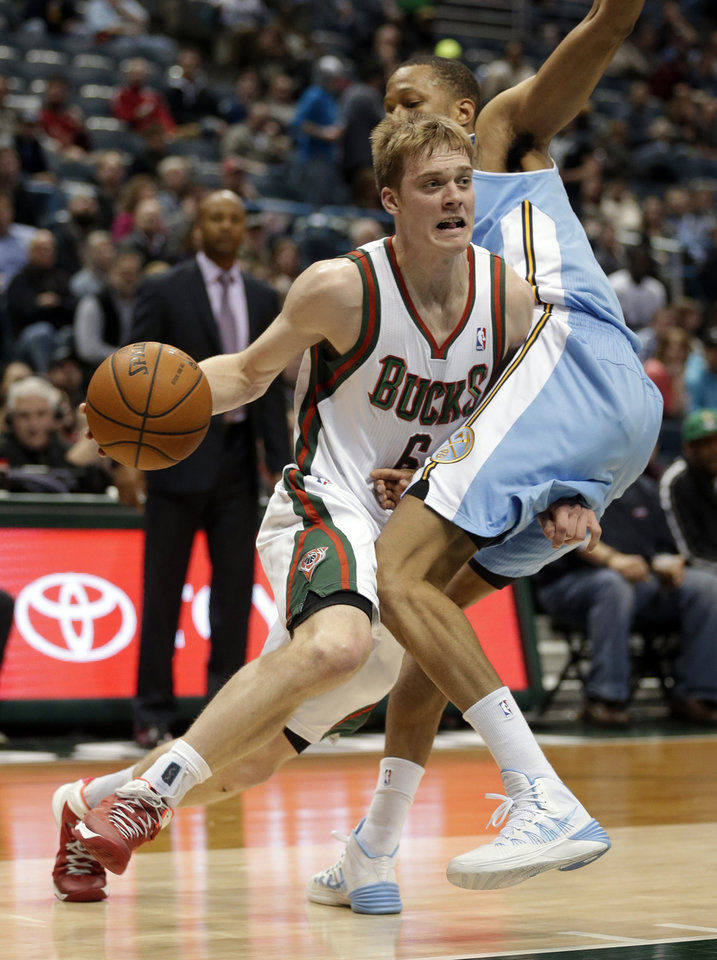 Photo - Milwaukee Bucks' Nate Wolters drives against the Denver Nuggets' Anthony Randolph, right, during the second half of an NBA basketball game Thursday, Feb. 20, 2014, in Milwaukee. (AP Photo/Jeffrey Phelps)