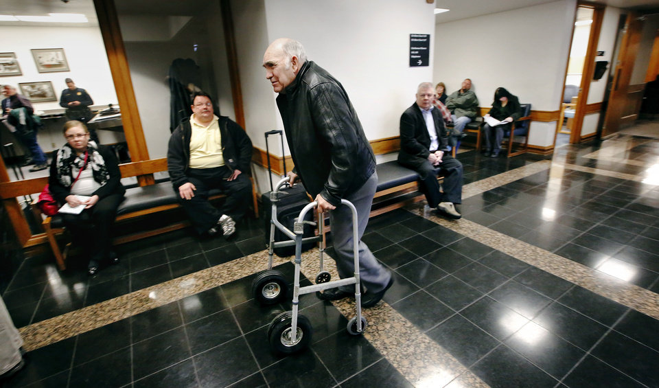 Photo - A man uses a walker as he passes others after his name was called to meet with an attorney Thursday at Workers' Compensation Court in the Denver Davison Building near the state Capitol in Oklahoma City. Photos by Jim Beckel, The Oklahoman