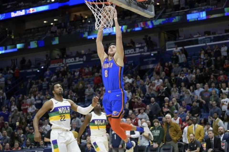 Photo -  Oklahoma City Thunder forward Danilo Gallinari goes up for a dunk next to New Orleans Pelicans center Derrick Favors (22) during Thursday night's game in New Orleans. OKC beat the Pelicans 123-118. [AP Photo/Matthew Hinton]