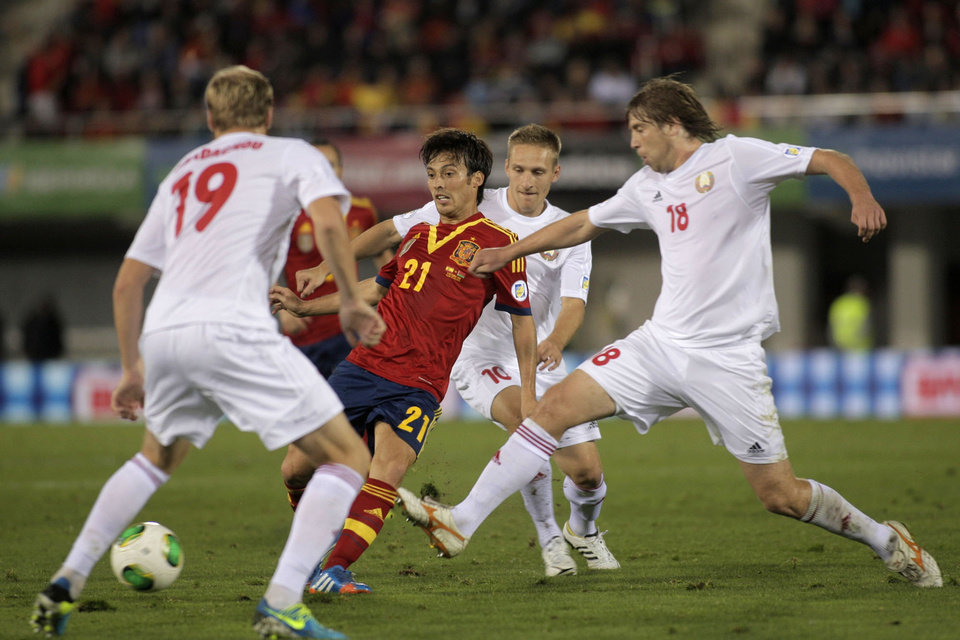 Photo - Spain's David Silva, center, vies for the ball with Belarus' Dmitry Verkhovtsov, right, and Maxim Bordachev during a 2014 World Cup Group I qualifying soccer match between Spain and Belarus at the  Iberostar Estadi in Palma de Mallorca, Spain, Friday Oct. 11, 2013. (AP Photo/Manu Mielniezuk)