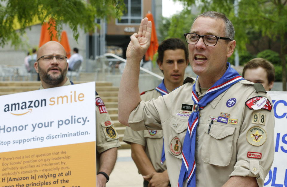 Photo - Geoffrey McGrath, right, a gay Boy Scout troop leader and Eagle Scout from Seattle, who had his membership in the Scouts revoked by the organization earlier this year, holds up the three fingers of the Scout Sign and recites the