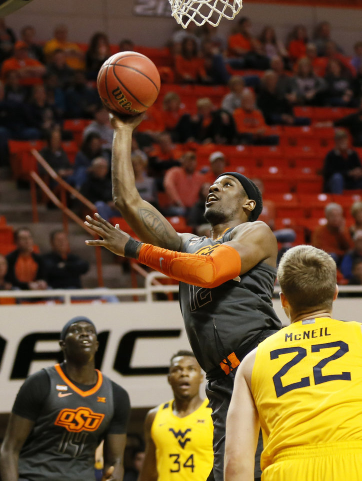Photo - Oklahoma State's Cameron McGriff (12) shoots as Oklahoma State's Yor Anei (14), left, West Virginia's Oscar Tshiebwe (34) and West Virginia's Sean McNeil (22) look on in the first half during a men's college basketball game between the Oklahoma State Cowboys and West Virginia Mountaineers at Gallagher-Iba Arena in Stillwater, Okla., Monday, Jan. 6, 2020. [Nate Billings/The Oklahoman]