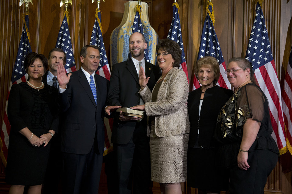 """FILE - In this Jan. 3, 2013, file photo Rep. Jackie Walorski, R-Ind., third from right, participates in a mock swearing-in ceremony with Speaker of the House Rep. John Boehner, R-Ohio, for the 113th Congress on Thursday, Jan. 3, 2013 in Washington. Persuading first-term Republicans in the House is President Barack Obama's toughest sell on military strikes against Syria. Many of the three dozen freshmen come from solidly GOP districts where voters have a deep distrust of the president on health care and immigration. """"I haven't heard a word about how the targeted, limited strikes protect America's national security,"""" Walorski said in an interview. """"How does this fit into a long-term plan for the Middle East? What is the endgame?"""" (AP Photo/ Evan Vucci, File)"""