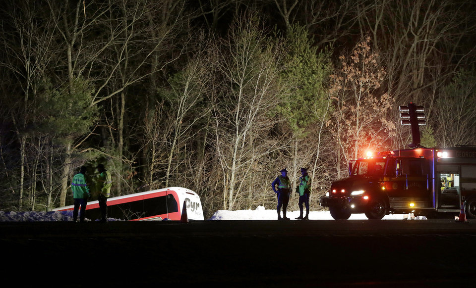 Police work at the scene in Georgetown, Mass. Tuesday, Feb. 26, 2013 where a bus carrying University of Maine basketball players crashed on Route 95, north of Boston, injuring the driver and several students. The driver was seriously injured and was taken by helicopter to a hospital, police said. Twenty-two students were being evaluated or treated for minor injuries. (AP Photo/Elise Amendola)