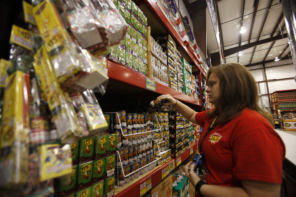 Melissa Minder stocks fireworks at TNT Fireworks Supercenter in Mustang, Tuesday, June 26, 2012.  Photo by Garett Fisbeck, The Oklahoman