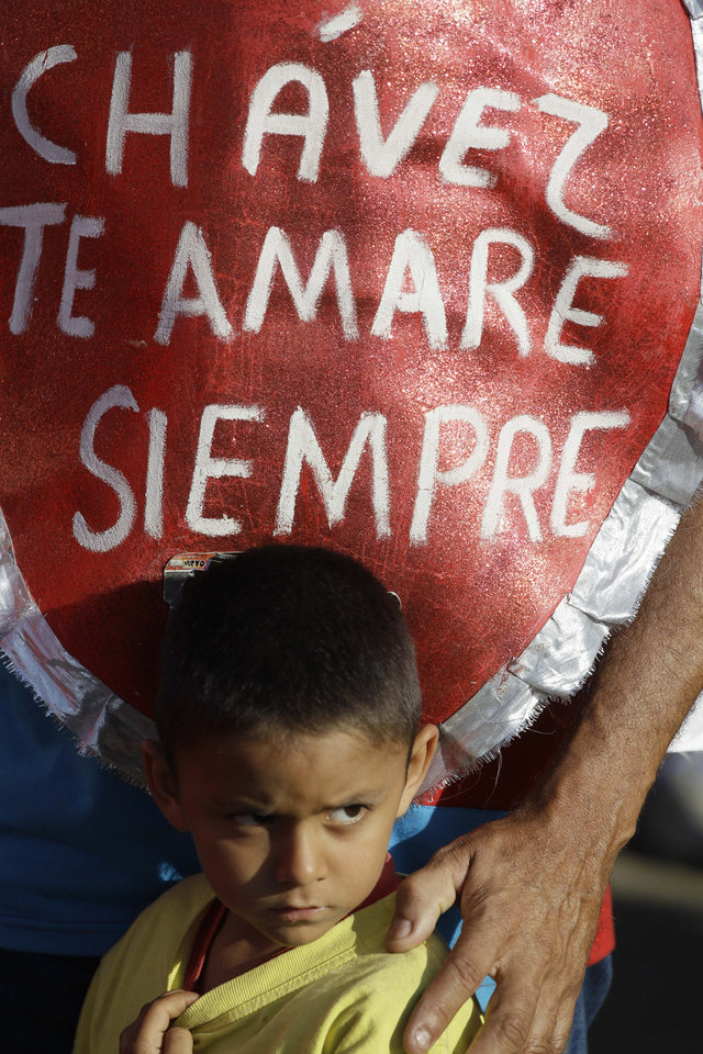 "A boy stands next to his father wearing a vest reading in Spanish ""Chavez I'll love you forever"" outside the military academy where a funeral ceremony will take place for Venezuela's late President Hugo Chavez in Caracas, Venezuela, Friday, March 8, 2013. With leaders from five continents on hand, Venezuela prepared for a day of distinctly different ceremonies, first the formal state funeral of Hugo Chavez, then the controversial swearing in of his anointed interim successor, who the opposition charges has no constitutional right to the job. (AP Photo/Fernando Llano)"