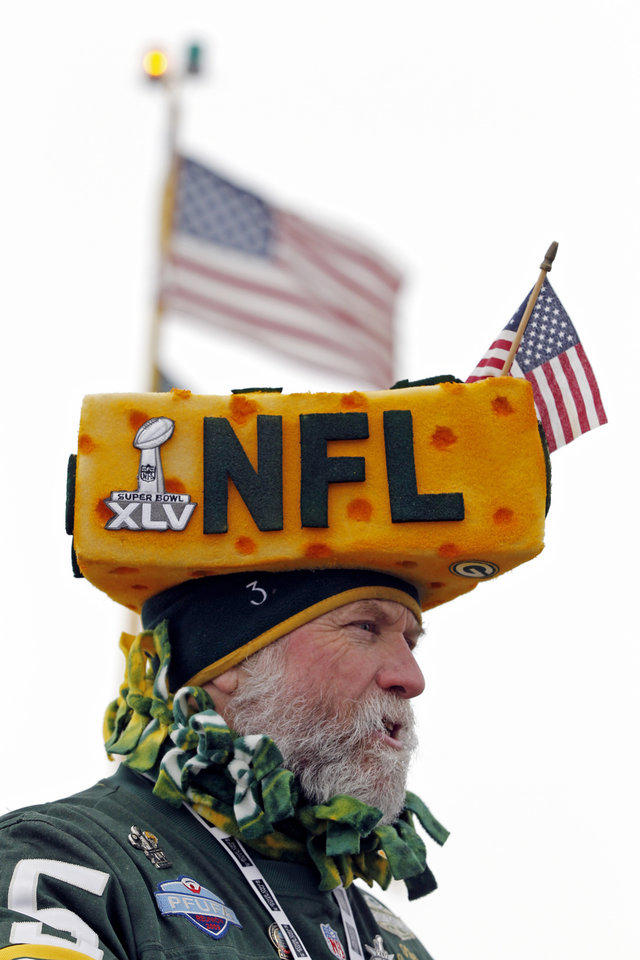 Photo - A Green Bay Packers wears a cheesehead as fans arrive at Lambeau Field before an NFL wild-card playoff football game between the Green Bay Packers and the San Francisco 49ers, Sunday, Jan. 5, 2014, in Green Bay, Wis. (AP Photo/Mike Roemer)