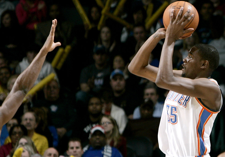 Photo - Oklahoma City's Kevin Durant puts up a shot against pressure from Atlanta's defense during their NBA basketball game at the OKC Arena in Oklahoma City on Friday, Dec. 31, 2010. The Thunder beat the Hawks 103-94. Photo by John Clanton, The Oklahoman