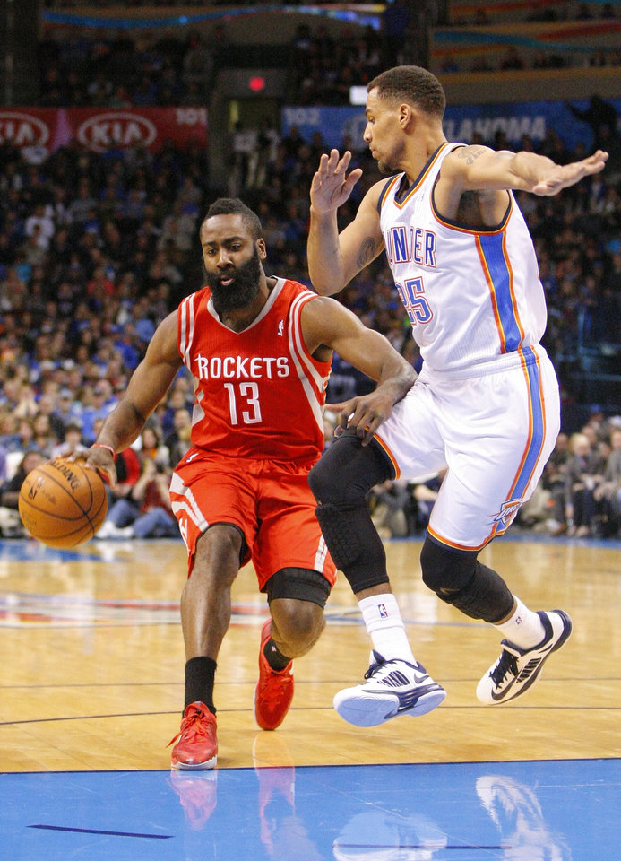 Photo - Houston Rockets guard James Harden, left, drives to the basket around Oklahoma City Thunder guard Thabo Sefolosha, right, during the first quarter of an NBA basketball game, Sunday, Dec. 29, 2013, in Oklahoma City. (AP Photo/Alonzo Adams)