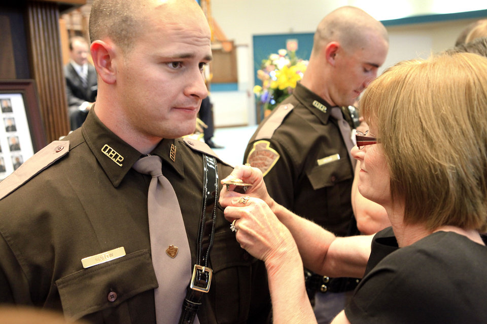 Photo - Oklahoma Highway Patrol trooper Jerrod Martin has his badge pinned on by his mother, Bobby, during his graduation ceremony. Photo By David McDaniel, The Oklahoman