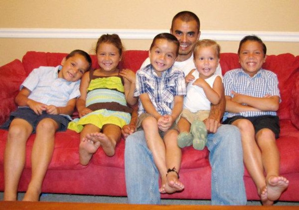 The Duran family poses in their Grove home. William Duran is raising his five children alone. From left: Dustin, 7, Javlynn, 4, Devon, 6, William Duran, 35, Dax, 22 months and Denton, 9. Sheila Stogsdill