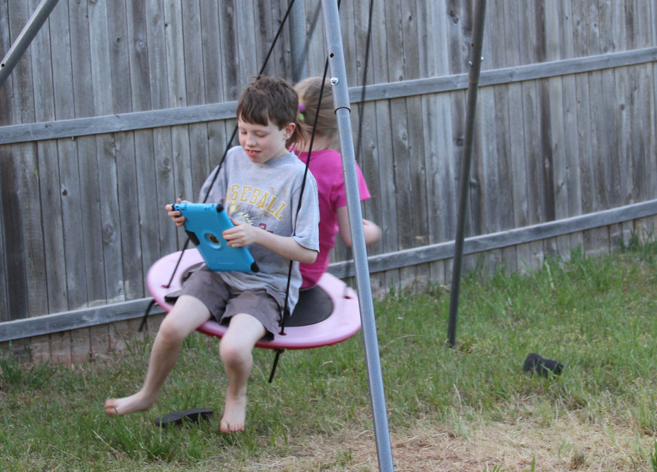 Danielle and Duane's son Harrison and 7-year-old daughter Libby play in the backyard of their Yukon home. Photo by Clifton Adcock, Oklahoma Watch  <strong></strong>