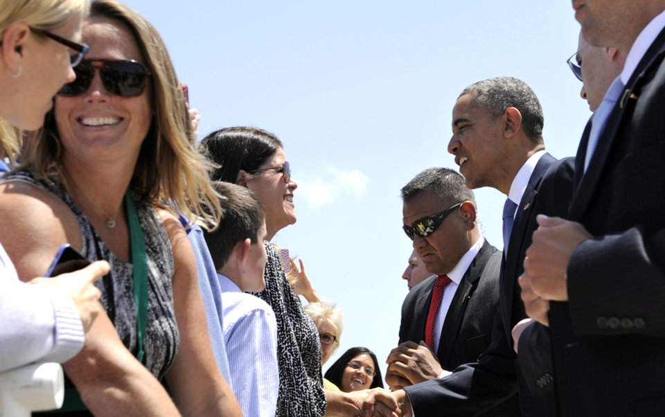 Photo - President Barack Obama greets people after arriving at Marine Corps Air Station Miramar, Calif., Thursday, May 8, 2014. Obama is spending 3 days in California raising money for the Democratic Party.  (AP Photo/Susan Walsh)