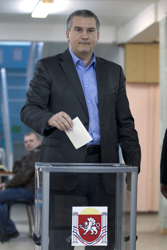 Photo - The head of Crimea's unrecognised Russian-backed government Sergei Aksyonov goes to cast his ballot at a polling station in Simferopol, Ukraine, Sunday, March 16, 2014. Residents of Ukraine's Crimea region are voting in a contentious referendum on whether to split off and seek annexation by Russia. (AP Photo/Ivan Sekretarev)