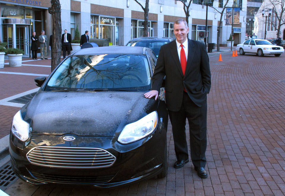 Photo - Indianapolis Mayor Greg Ballard talks poses with electric and plug-in hybrid vehicles like these shown following an announcement that the city will replace it's fleet of cars with similar type vehicles in Indianapolis, Wednesday, Dec. 12, 2012. Indianapolis plans to replace its entire fleet with electric and plug-in hybrid vehicles by 2025.  (AP Photo/Rick Callahan)