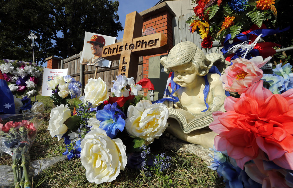 Photo - HIGH SCHOOL FOOTBALL: CHRISTOPHER LANE MURDER / MEMORIAL: The spot on Country Club Drive where Christopher Lane was found is marked by a statue, cards, a wooden carved cross and other items on Thursday, Aug. 22, 2013 in Duncan, Okla.  Photo by Steve Sisney, The Oklahoman