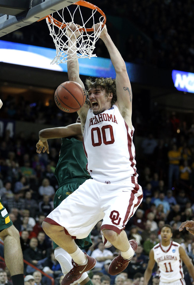Photo - Oklahoma's Ryan Spangler (00) dunks the ball during the NCAA men's basketball tournament game between the University of Oklahoma and North Dakota State at the Spokane Arena in Spokane, Wash., Thursday, March 20, 2014. Oklahoma home lost 80-75. Photo by Sarah Phipps, The Oklahoman