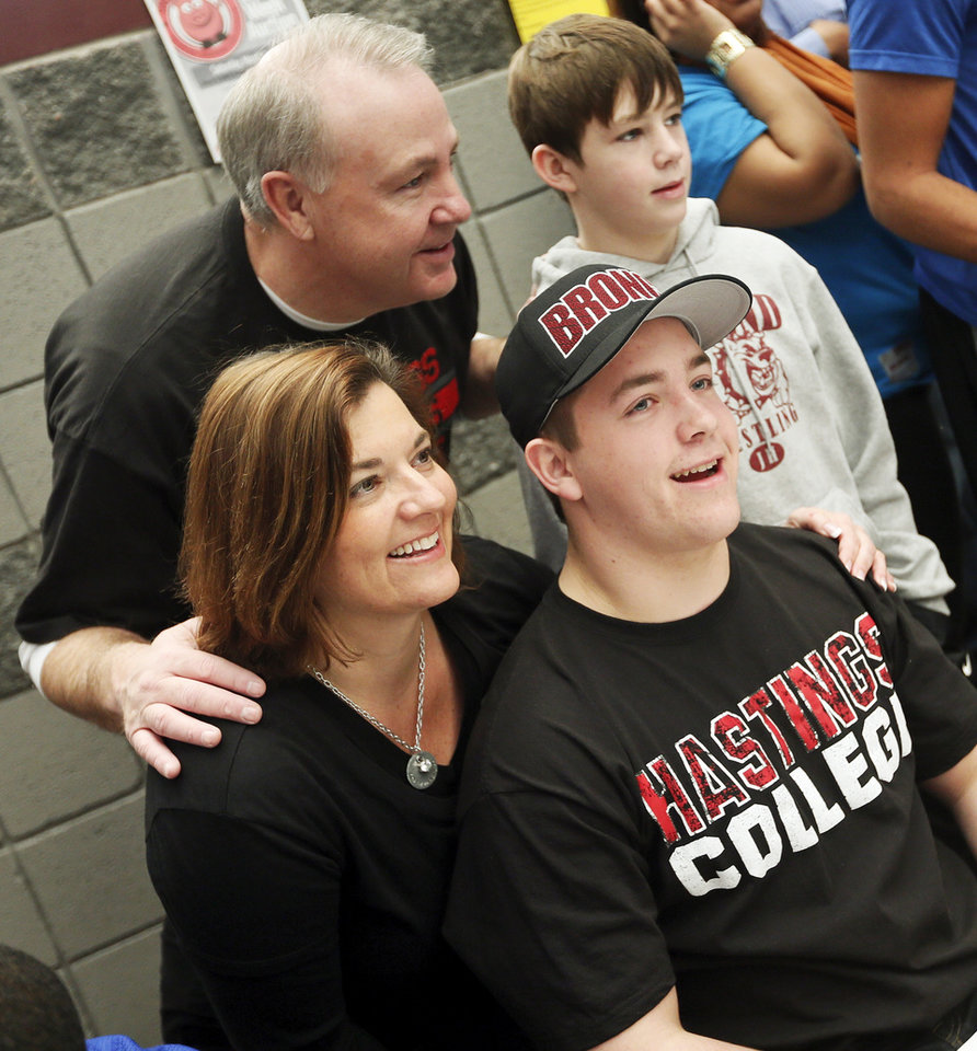 Photo - Sam Rolle, lower right, poses for a photo with his mother, Michelle Rolle, father, David Rolle, and brother, Peter Rolle, after signing to play football at Hastings College during the college signing day ceremony for student athletes at Edmond Memorial High School in Edmond, Okla., Wednesday, Feb. 5, 2014. Photo by Nate Billings, The Oklahoman