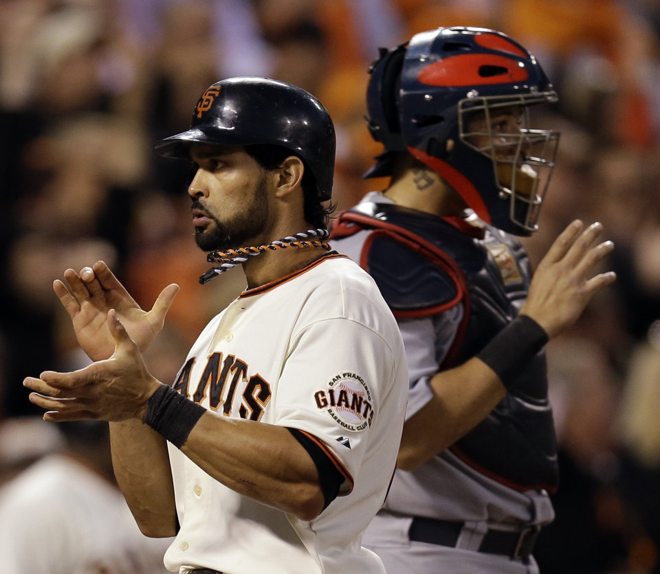 Photo -   San Francisco Giants' Angel Pagan reacts in front of St. Louis Cardinals catcher Yadier Molina after scoring on a hit by Marco Scutaro during the fourth inning of Game 2 of baseball's National League championship series Monday, Oct. 15, 2012, in San Francisco. (AP Photo/David J. Phillip)