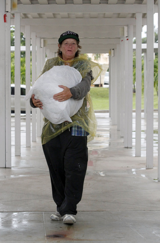 Photo -   Cheri Senecal walks with a bag of personal items to a shelter in Key West, Fla., Saturday, Aug. 25, 2012 as she prepares for Tropical Storm Isaac, Saturday, Aug. 25, 2012. Isaac's winds are expected to be felt in the Florida Keys by sunrise Sunday morning. (AP Photo/Alan Diaz)