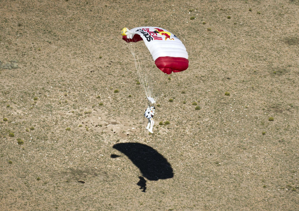 In this photo provided by Red Bull, pilot Felix Baumgartner of Austria lands in the desert after his successful jump on Sunday, Oct. 14, 2012 in Roswell, N.M. Baumgartner came down safely in the eastern New Mexico desert minutes about nine minutes after jumping from his capsule 128,097 feet, or roughly 24 miles, above Earth (AP Photo/Red Bull, Predrag Vuckovic)  ORG XMIT: NY207
