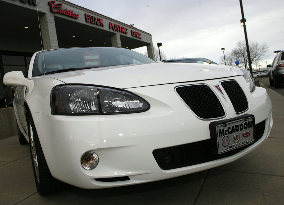 """Photo - File-This Feb. 18, 2007, file photo shows an unsold 2006 Grand Prix sedan sitting outside a General Motors dealership in Boulder, Colo.  General Motors' safety crisis worsened on Monday, June 30, 2014, when the automaker added 8.2 million vehicles to its huge list of cars recalled over faulty ignition switches. The latest recalls cover seven vehicles, including the Chevrolet Malibu from 1997 to 2005 and the Pontiac Grand Prix from 2004 to 2008. The recalls also cover a newer model, the 2003-2014 Cadillac CTS. GM said the recalls are for """"unintended ignition key rotation.""""  (AP Photo/David Zalubowski, File)"""