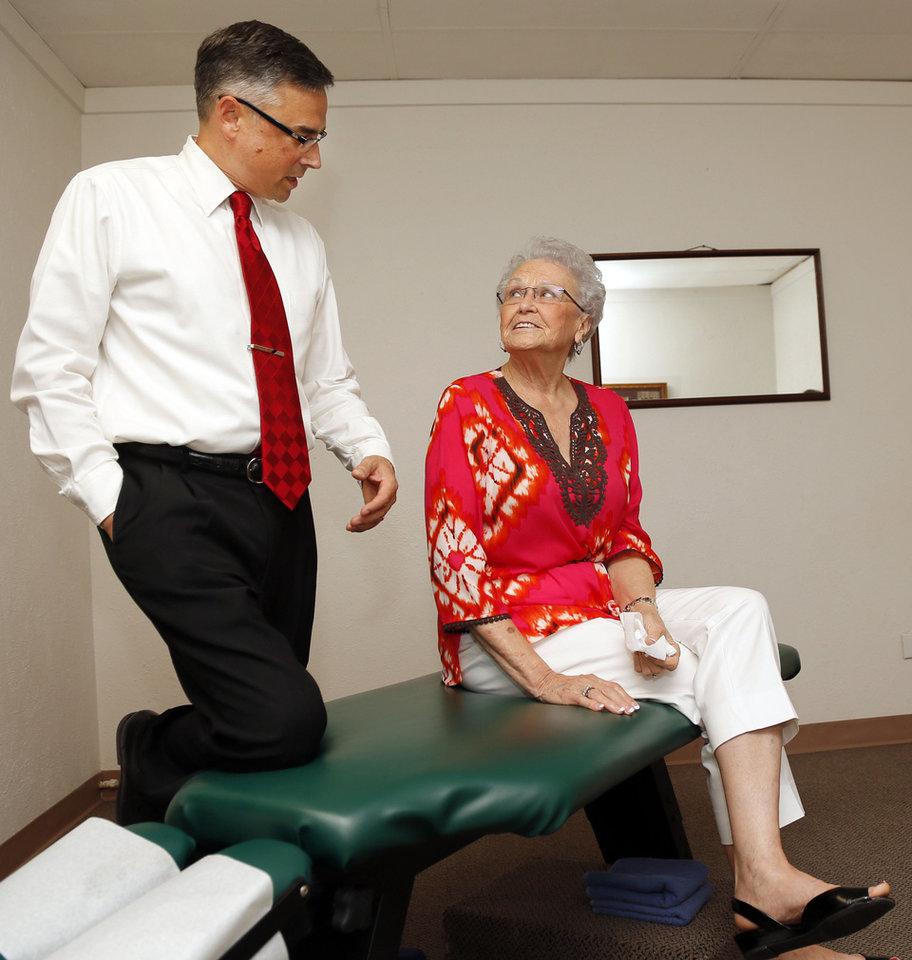 Photo - Dr. Gregory S. Howard, a chiropractor, talks with patient Ruby Walker, 78, at his office in Frederick, Okla. Walker was Howard's first patient when he began his practice in Frederick about 18 years ago.  NATE BILLINGS - NATE BILLINGS