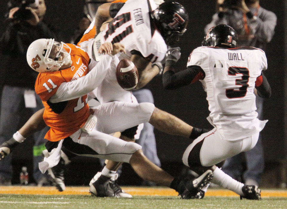 Photo - Zac Robinson (11) falls to the ground after his collison with Jamar Walls (3) during the college football game between Oklahoma State University (OSU) and Texas Tech University at Boone Pickens Stadium in Stillwater, Okla. Saturday, Nov. 14, 2009. Photo by Doug Hoke, The Oklahoman