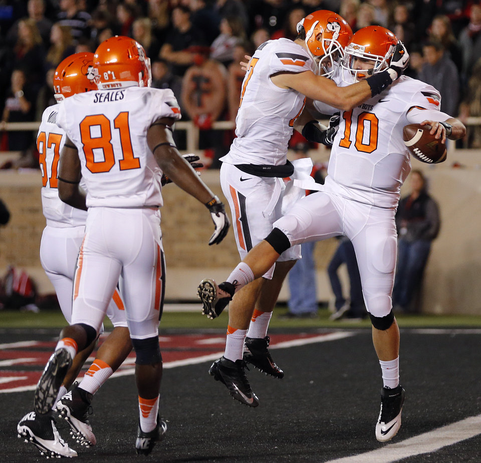 Oklahoma State 's Clint Chelf (10) and Charlie Moore (17) celebrate a touchdown run by Chelf during the college football game between the Oklahoma State University Cowboys (OSU) and the Texas Tech University Red Raiders (TTU) at Jones AT&T Stadium in Lubbock, Tex. on Saturday, Nov. 2, 2013.  Photo by Chris Landsberger, The Oklahoman