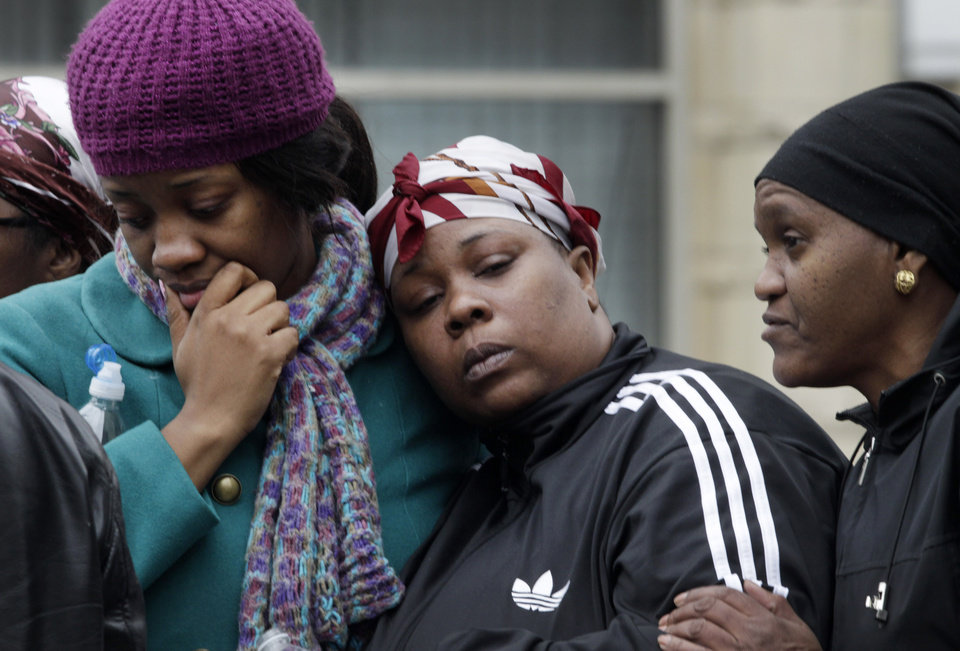 Photo - Alecia Thomas, left, is comforted by her friend Shivon Dollar, center, after she lost her home following an explosion that leveled two apartment buildings in the East Harlem neighborhood of New York, Wednesday, March 12, 2014. The blast happened after a neighbor reported smelling natural gas. The woman on the right is unidentified. (AP Photo/Mark Lennihan)