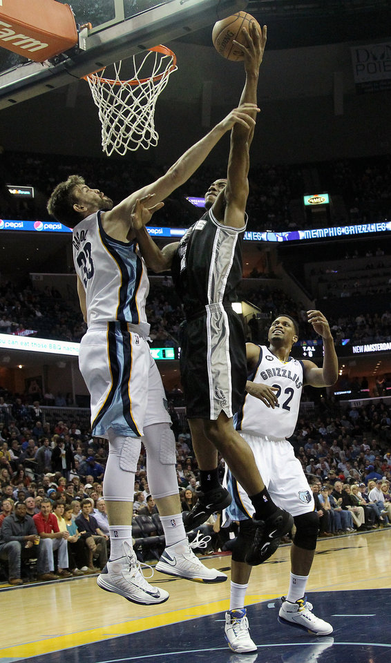 Photo - San Antonio Spurs guard Kawhi Leonard (2) goes to the basket and is fouled by Memphis Grizzlies center Marc Gasol (33), of Spain, with Grizzlies forward Rudy Gay (22) watching in the first half of an NBA basketball game on Friday, Jan. 11, 2013, in Memphis, Tenn. (AP Photo/Lance Murphey)