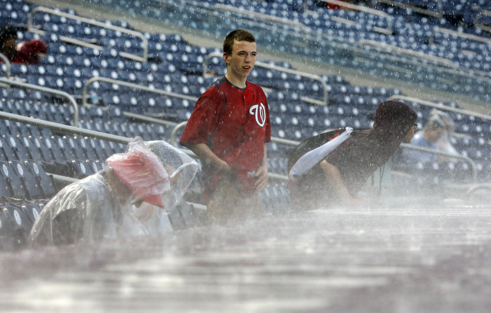 Photo - A few fans brave the rain during a rain delay in the sixth inning of a baseball game between the Washington Nationals and the Cincinnati Reds at Nationals Park on Wednesday, May 21, 2014, in Washington. (AP Photo/Alex Brandon)