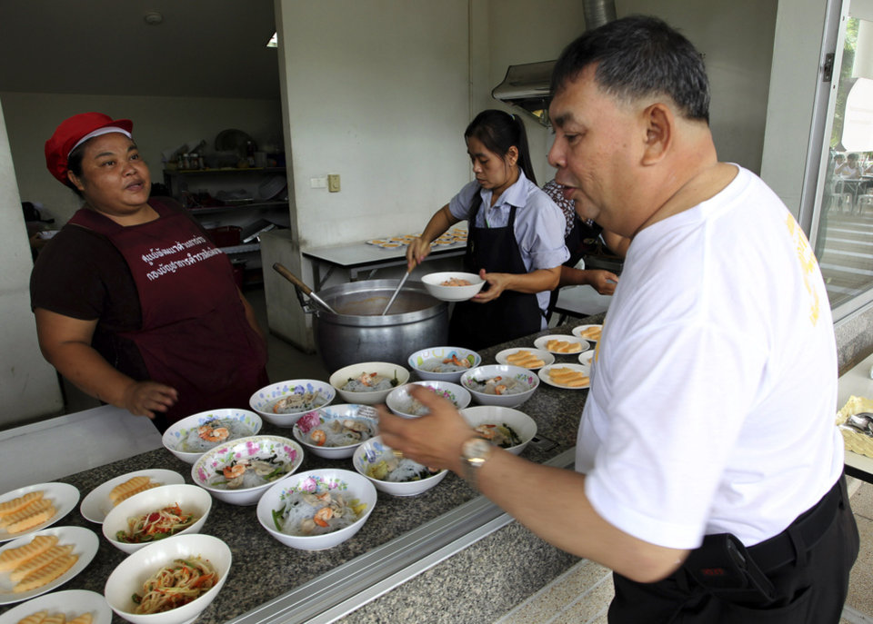 Photo - In this photo taken Thursday, July 4, 2013, a Thai police officers Lt. Winya Thengnimitr, right, picks a small portion of lunch at a police training center in Bangkok, Thailand. As part of a national effort to reduce the numbers of overweight officers, Thailand has opened a 12-day boot camp to get police into shape. This week, 60 overweight officers from around the country were sent to suburban Bangkok for dawn-to-dusk exercise and lecture programs on living more healthy. (AP Photo/Apichart Weerawong)