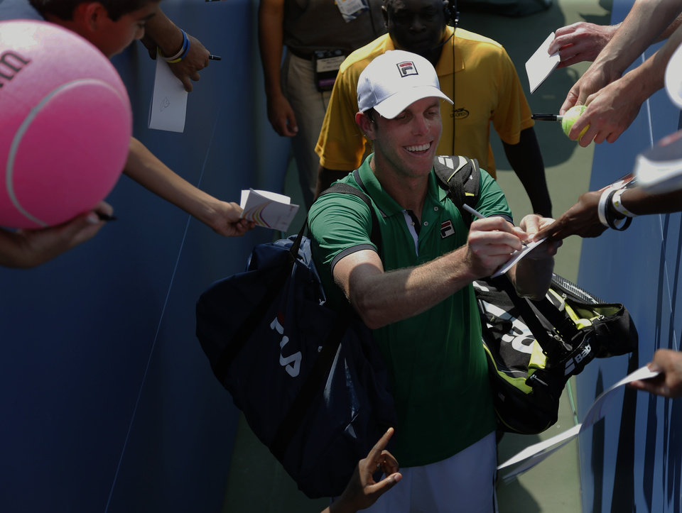 Photo - Sam Querrey, of the United States, signs autographs for fans during the first round of the 2014 U.S. Open tennis tournament, Tuesday, Aug. 26, 2014, in New York. (AP Photo/Elise Amendola)